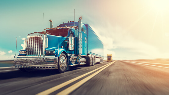 A low angle view of a steel blue tractor-trailer traveling down an open road