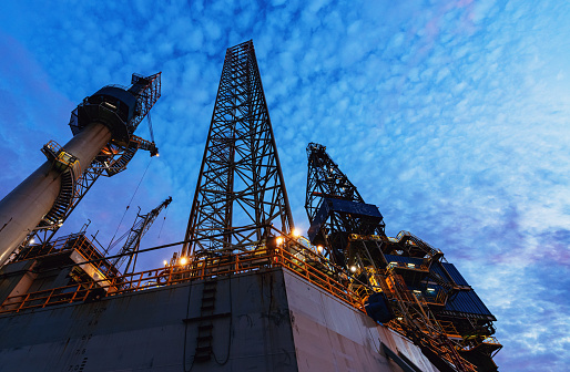 A jackup offshore oil drilling rig is docked at port for maintenance & repairs prior to reassignment